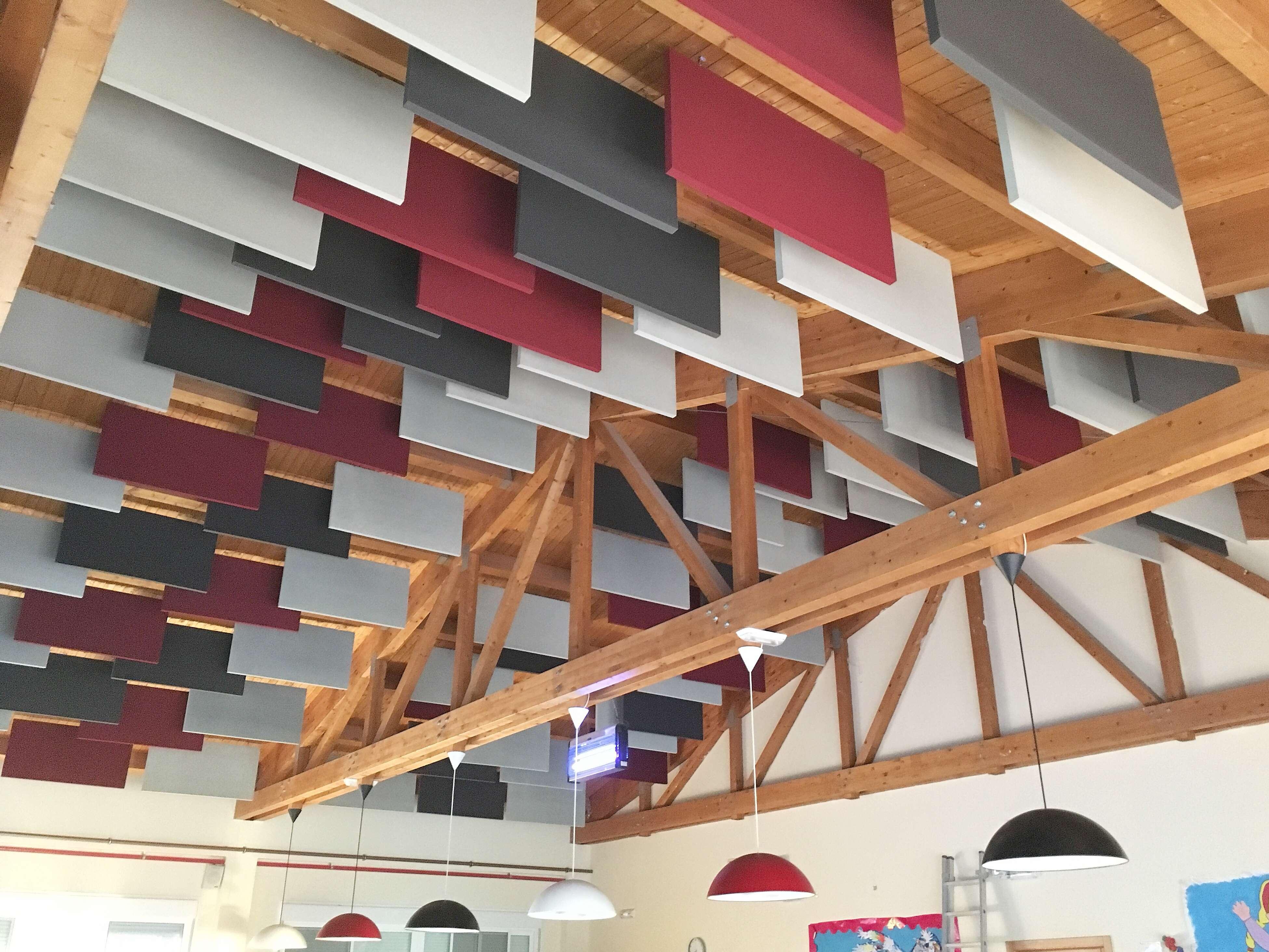 Baffles acusticos de colores colgados de un techo de maderad. Reducen el ruido en el comedor.