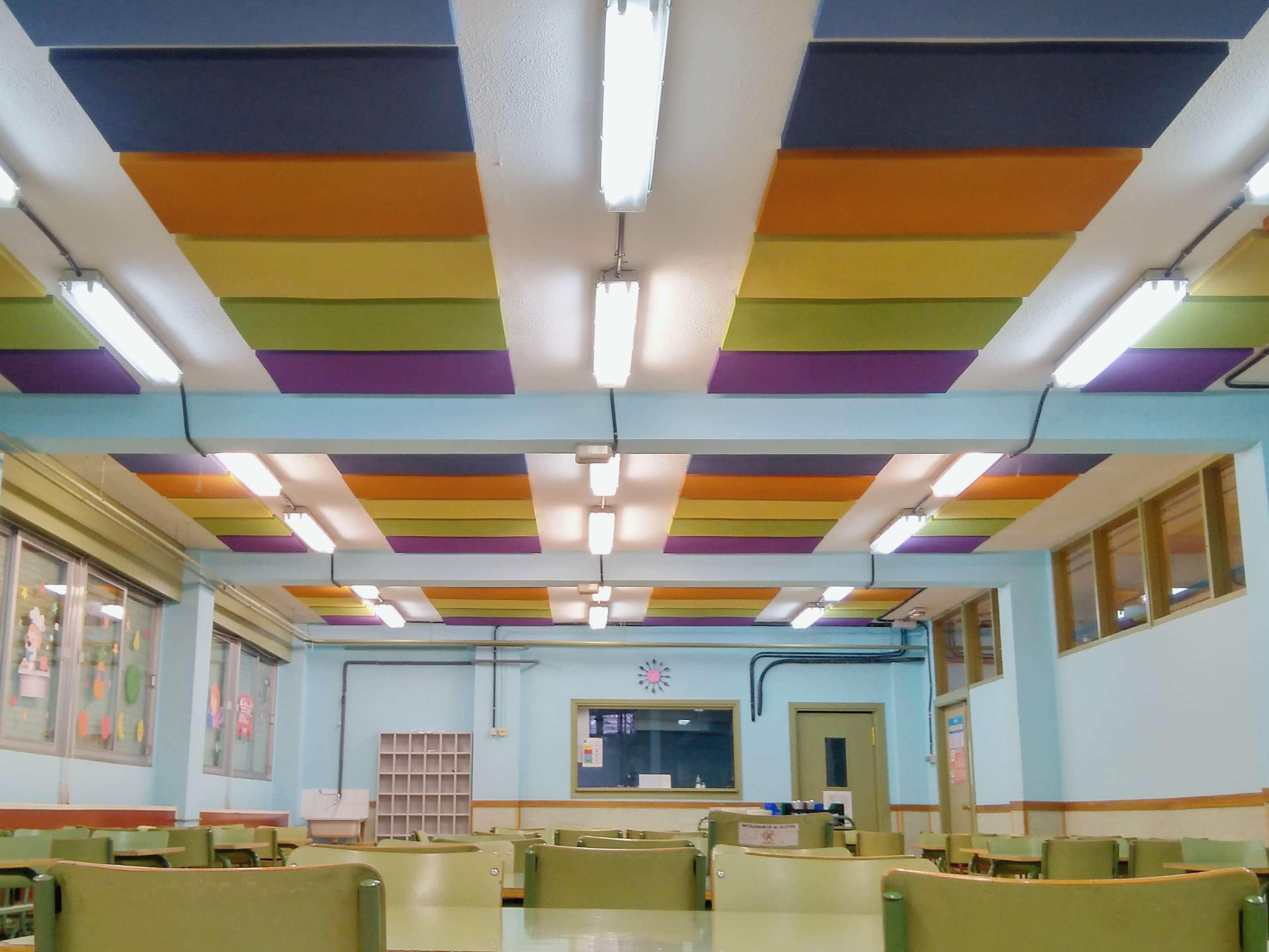 Combinacion de paneles acusticos de diferentes medidas y colores para reducir el ruido en un comedor escolar.