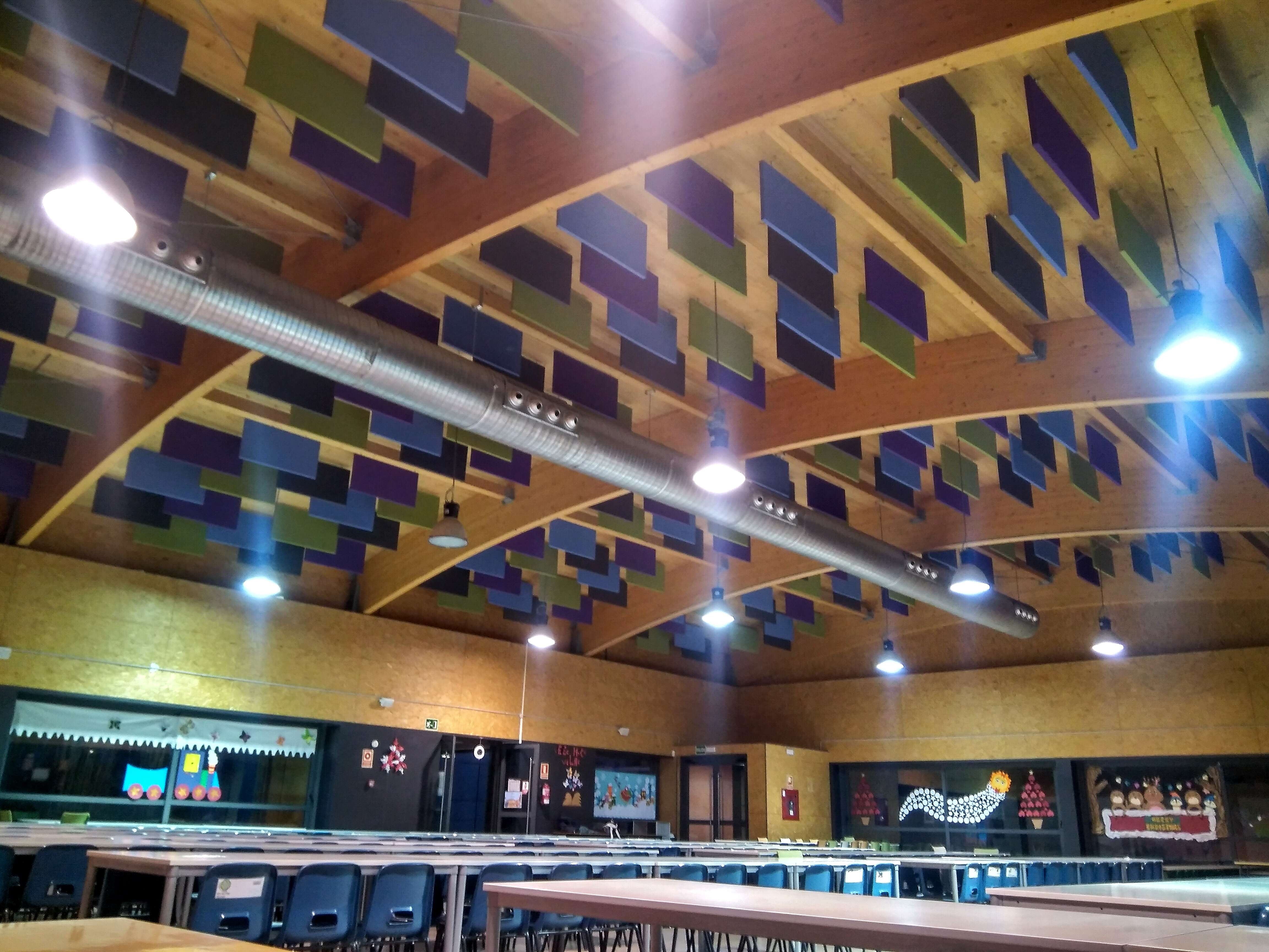 Paneles acusticos colgados en techo curvado de madera de un comedor escolar
