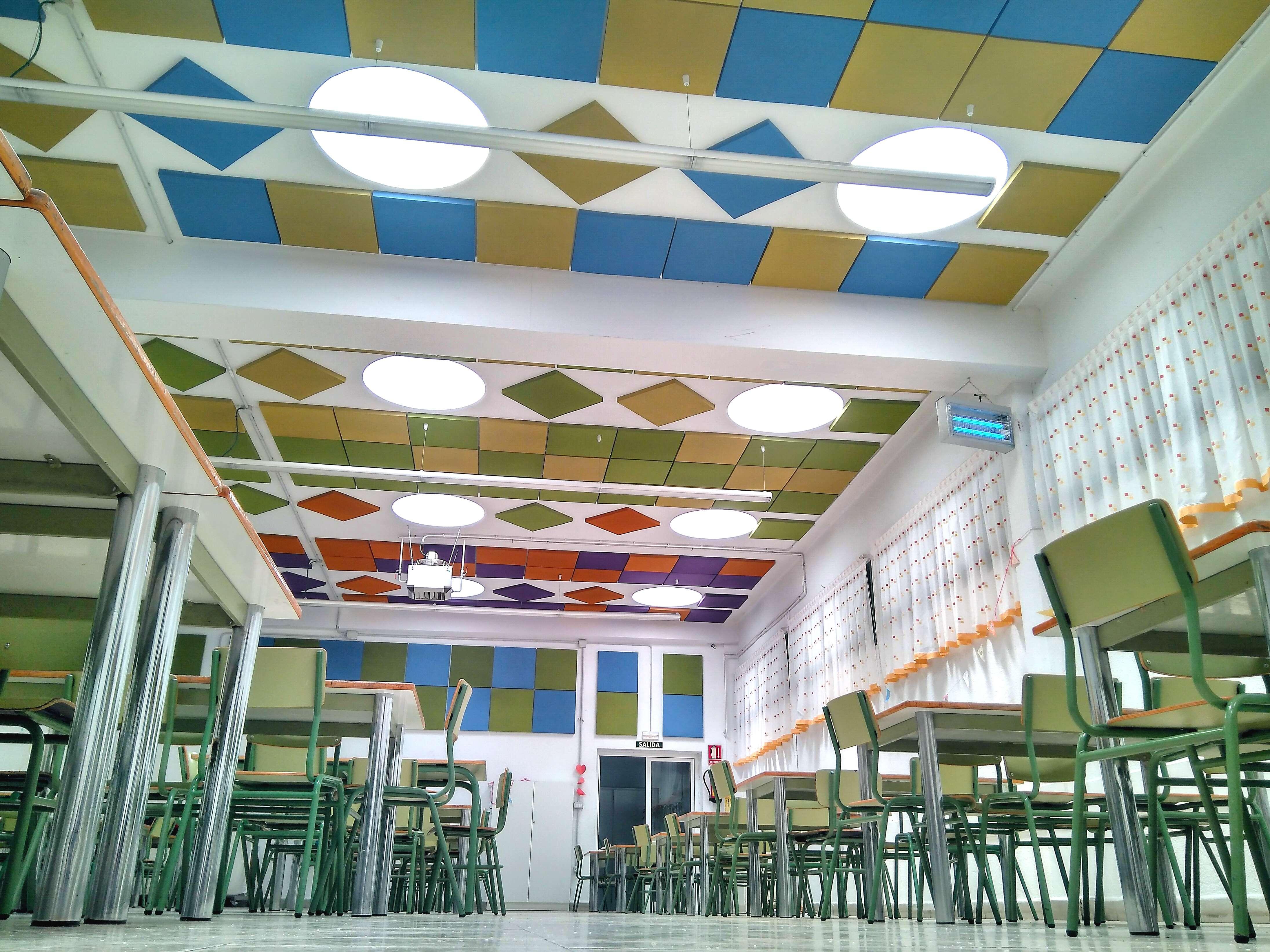 Combinacion de paneles acusticos de colores combinando formas decorativas en comedor escolar